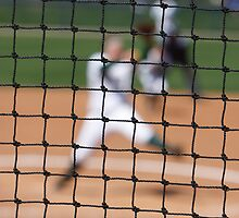 Softball Game - Blurred Pitcher Seen Thorugh the Focused Backstop Net by Buckwhite