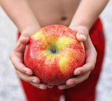 Child holding large red apple by monicamurphy