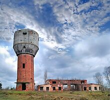 ruins of old water-tower on autumn landscape by Sergieiev