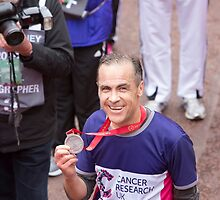 Neil Plumridge crosses the finish line at the Virgin money London Marathon by Keith Larby
