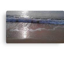 A gentle wave rolls onto a beach Canvas Print