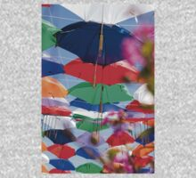 Colourful umbrellas strung up together on a blue sky background  Kids Tee