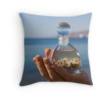 Hands hold a bottle with seashells on the beach Throw Pillow