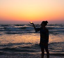 woman holds the sun as it sets in the palm of her hand  by PhotoStock-Isra