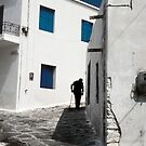 Old man turning the corner in Mykonos Greece by milton ginos