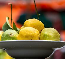 A plate with Fresh Lemons and limes with dew drops  by PhotoStock-Isra