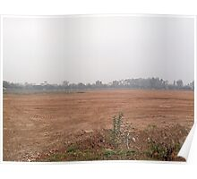 A wide open dusty field surrounded by cars, trees and buildings Poster