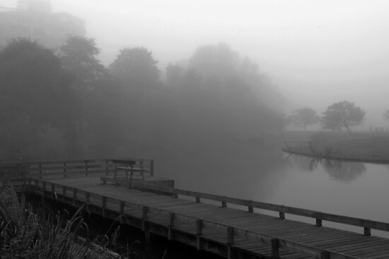 Lonely bench on misty pier by steppeland