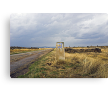 old pilgrim's trail marker beneath stormy clouds Canvas Print