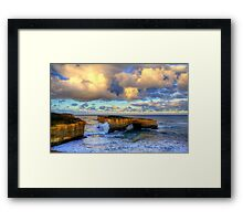 A wave crashes the London Arch at sunrise Framed Print