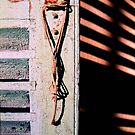 Hanging rope, old shutter and shadows by Silvia Ganora