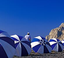 Man Among Beach Umbrellas, Santorini (Greece)  by Petr Svarc