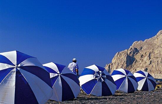 Man Among Beach Umbrellas, Santorini (Greece)  by Petr Svarc