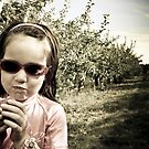 A girl eats a fresh apple from an orchard on a farm by Jean Beaudoin