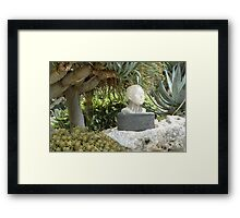 A Sculpted Head In Amongst The Cacti Framed Print