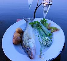Fresh fish catch on a plate with vegetables by jekuratodistaja