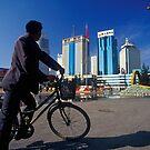 Man on Bicycle and Modern High-rises of Kunming, China (Yunnan)  by Petr Svarc