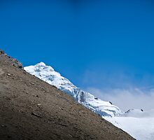 Trekkers walking up hill side with snow capped mountain in the background  by Erdj