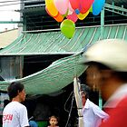 Balloons on a busy street - Vietnam by biancamarks