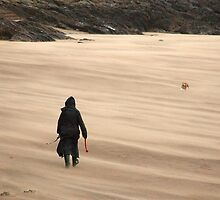 Walking the dog in the wind on a sandy beach by Christopher Ware