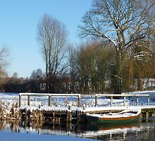 A snow covered small boat moored on a river by johnny2sheds