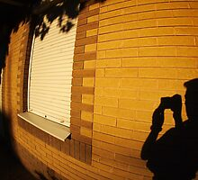 The shadow of a man on the illuminated wall of a house by vladromensky