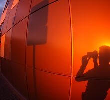 The shadow of a man on a red-orange wall, who photographs a road sign by vladromensky