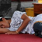 Balinese boy sleeping on a temple pagoda  by Michael Brewer