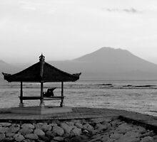 Lone figure in beachside pagoda, sacred mountain Gunung Agung in background. Bali, Indonesia by Sheldon Levis