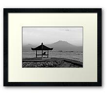 Lone figure in beachside pagoda, sacred mountain Gunung Agung in background. Bali, Indonesia Framed Print