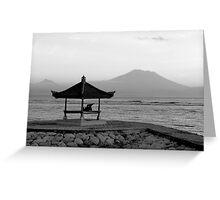 Lone figure in beachside pagoda, sacred mountain Gunung Agung in background. Bali, Indonesia Greeting Card