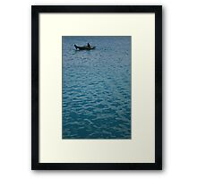 Solitary sailor in a little wooden boat. Framed Print