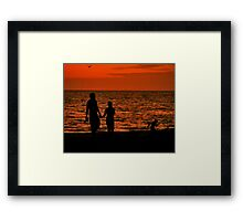 Silhouette of young couple with child Framed Print