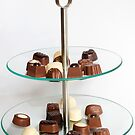 Chocolate candies on dish. by PhotoGrafin