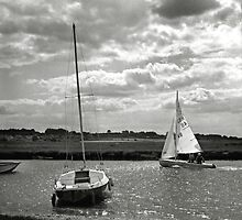 A yacht returns to harbour at Blakeney, Norfolk, UK by Richard Flint