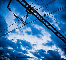Electric wires railroad against blue cloudy sky by Tycho's Eye  Photography