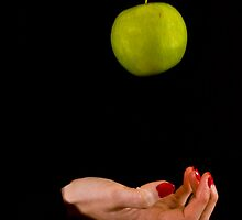 Female hand throwing a green apple by Gabor Pozsgai
