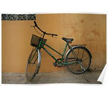 Green bike on yellow wall Poster