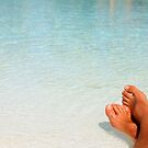 Close up of male legs on white sandy beach in the Maldives by Bruno Beach