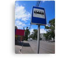 Road sign with a picture of a bus stop on a city street Canvas Print