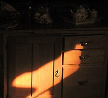 Morning sunlight on wooden cabinet by Patty Gross