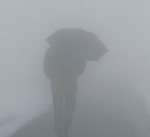Man walking away with umbrella in the fog by Michael Brewer