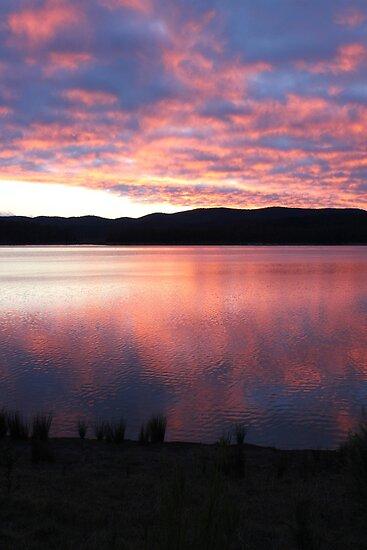 pink sky over blue rock by waterchild