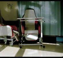 In the corner of the hospital room 2 red and white chairs sit encased between blue curtains..  by madworld