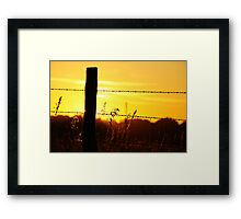 Silhouetted fencepost at sunrise Framed Print