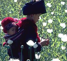 Mien woman and baby slitting opium poppy by John Spies