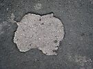 Spooky looking face in the pavement by buttonpresser