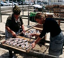 The Ladies Of Nazaré Tend Their Fish by rorycobbe