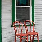 Two Orange Chairs Outside a Green Bordered Window by Gerda Grice