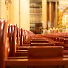 Church benches with alter in the background by Matt Lipa